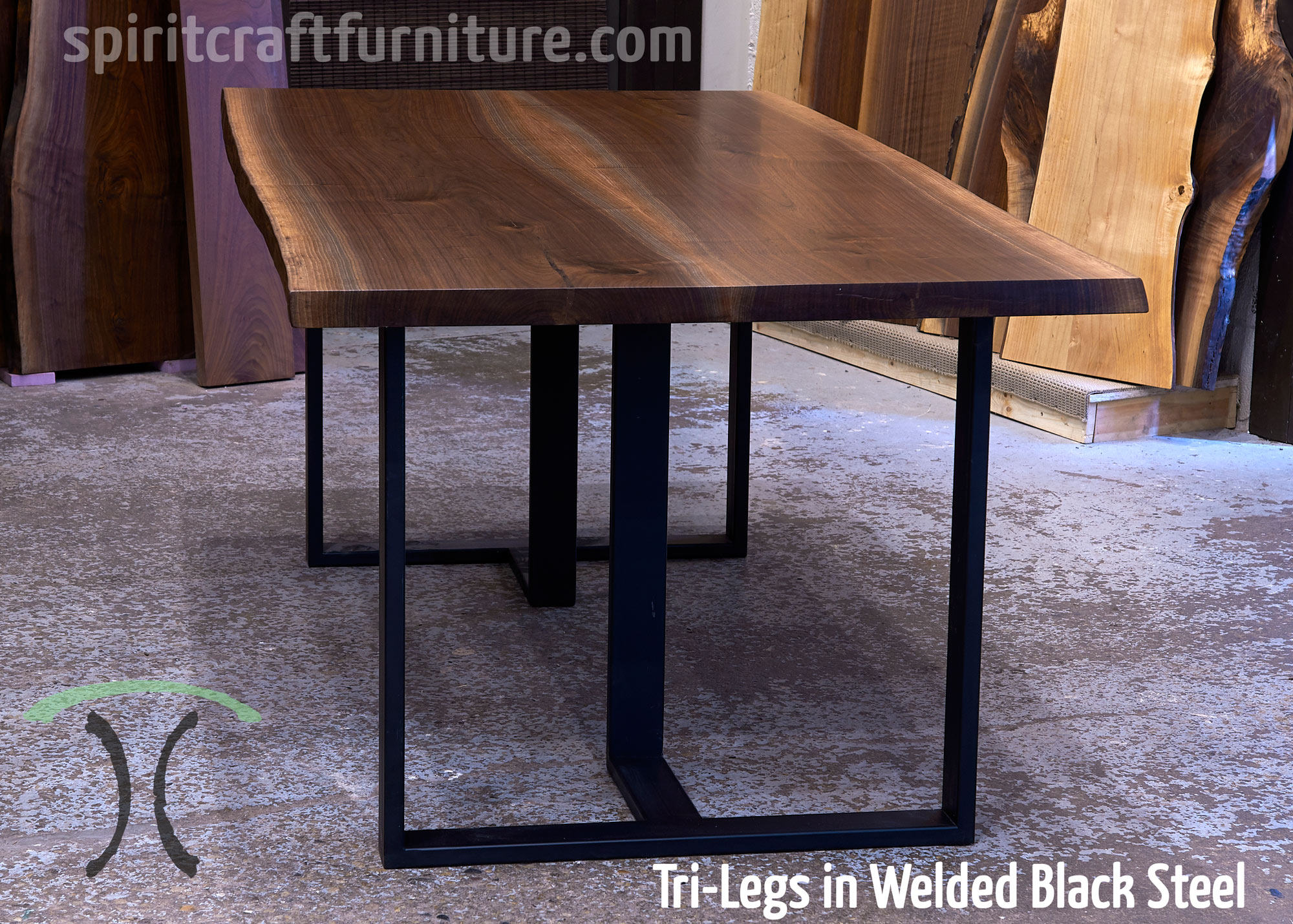 Custom made 1 x 3 tri-legs, in welded steel painted black with live edge walnut slab table top.