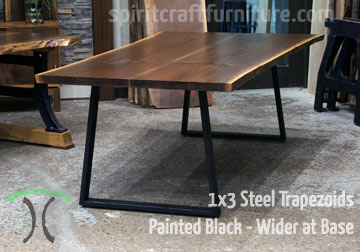 Custom made 1 x 3 steel trapezoid legs, wider at the base, painted black on live edge walnut table top.