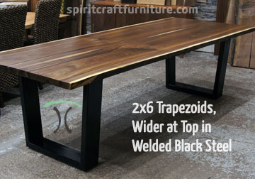 Custom made 2 x 6 steel trapezoid legs, wider at the top, painted black on live edge walnut table top.