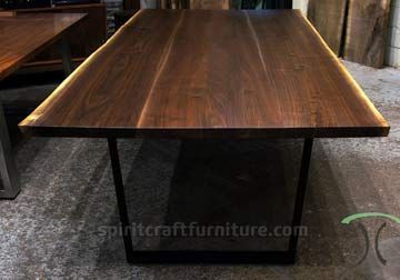 Live edge dining conference table in solid book-matched Black Walnut on display at our retail furniture store in Chicago area, East Dundee, Illinois