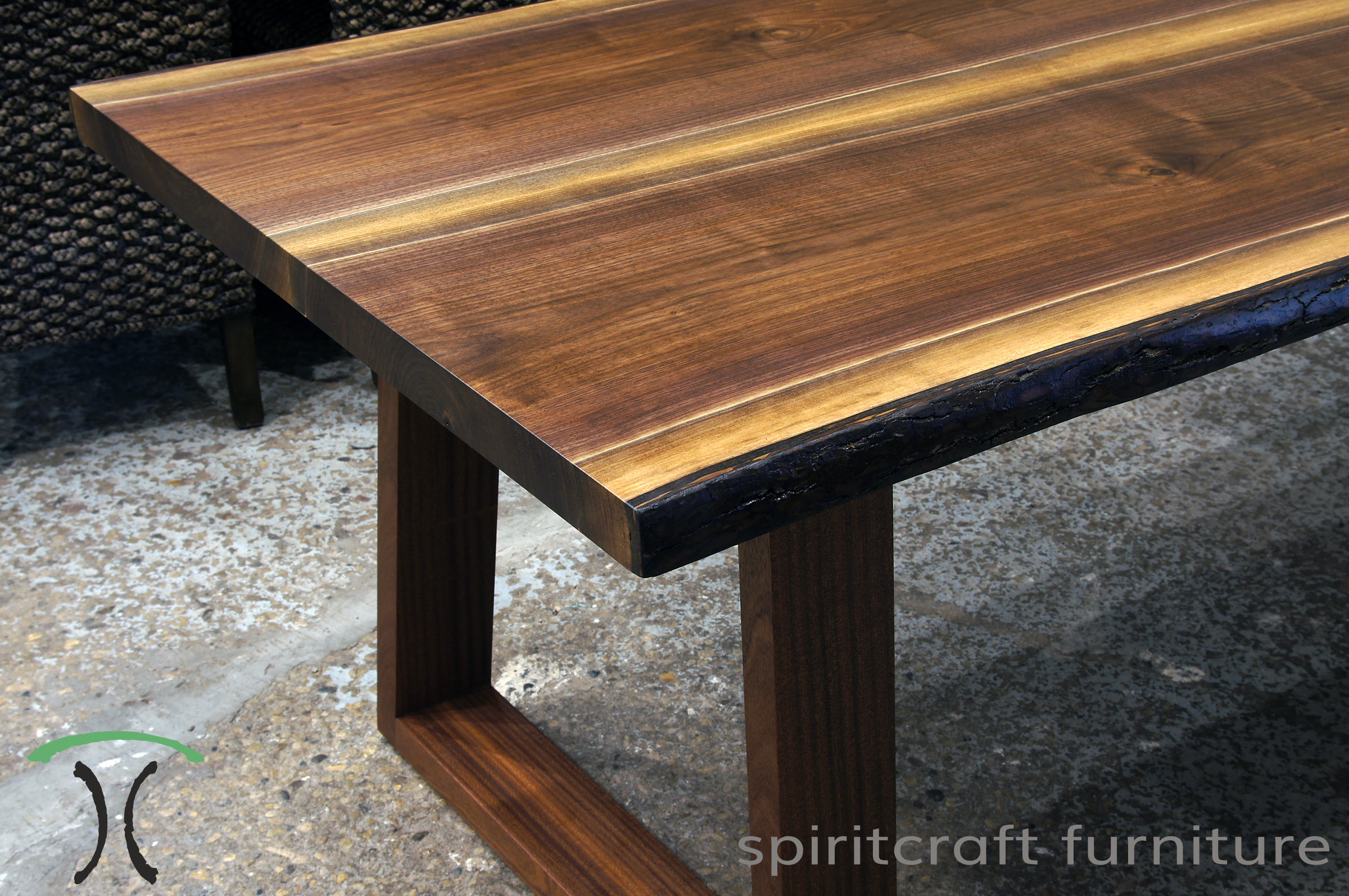 Live edge dining, conference table or desk in solid Black Walnut on Sapele inverted trapezoid legs, displayed at our retail slab furniture store in Chicago area, East Dundee, Illinois