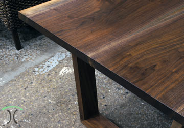 Black Walnut live edge dining table on wooden trapezoid legs at Chicago area furniture Company in East Dundee, IL.