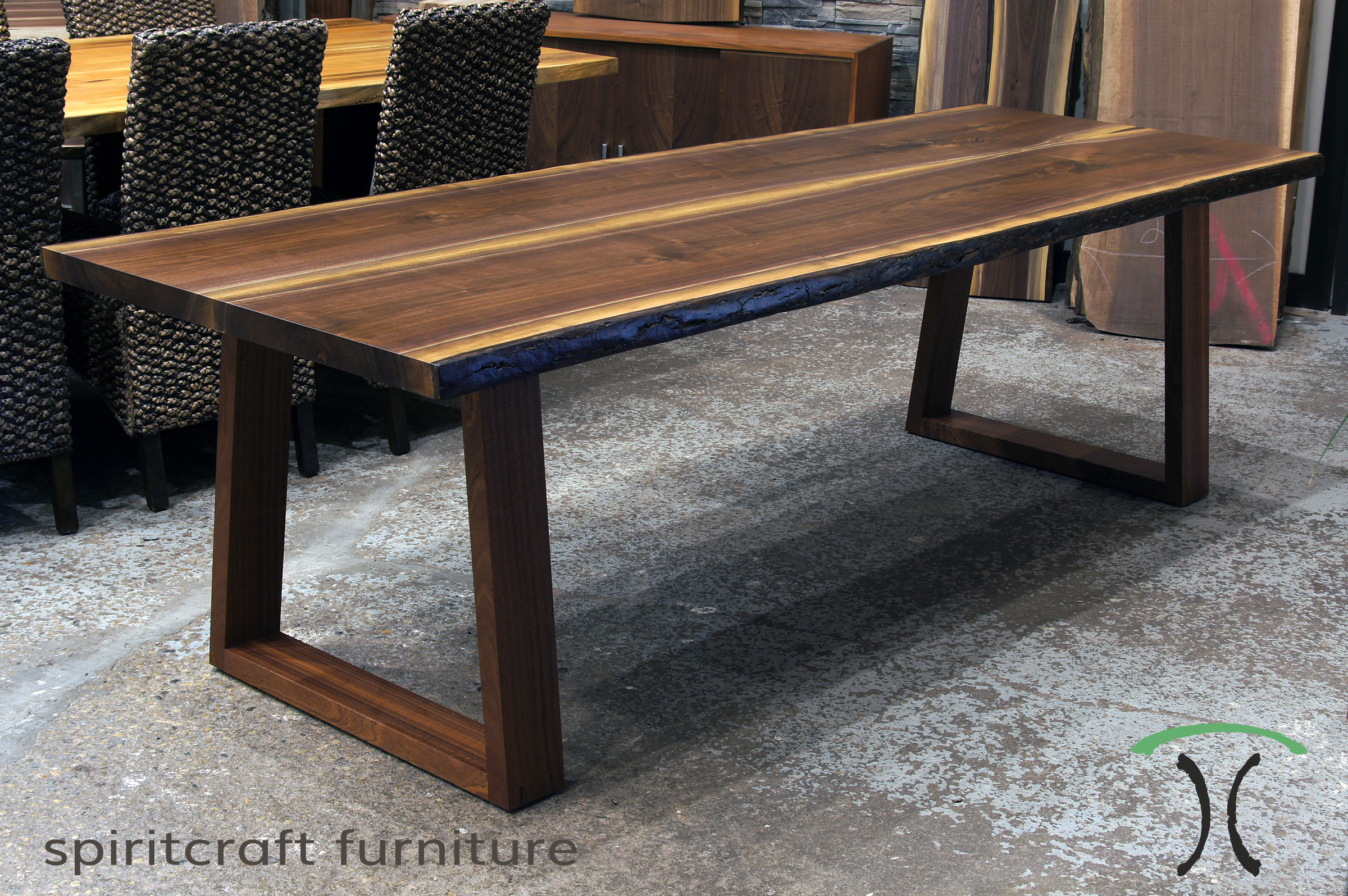 Black Walnut live edge dining table on inverted Sapele trapezoid legs at Living Edge Furniture Company in East Dundee, IL.