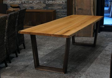 Live edge slab Cherry dining table with mid century style open trapezoidal legs in Walnut at Spiritcraft Furniture Store in Chicago suburbs, East Dundee, IL.