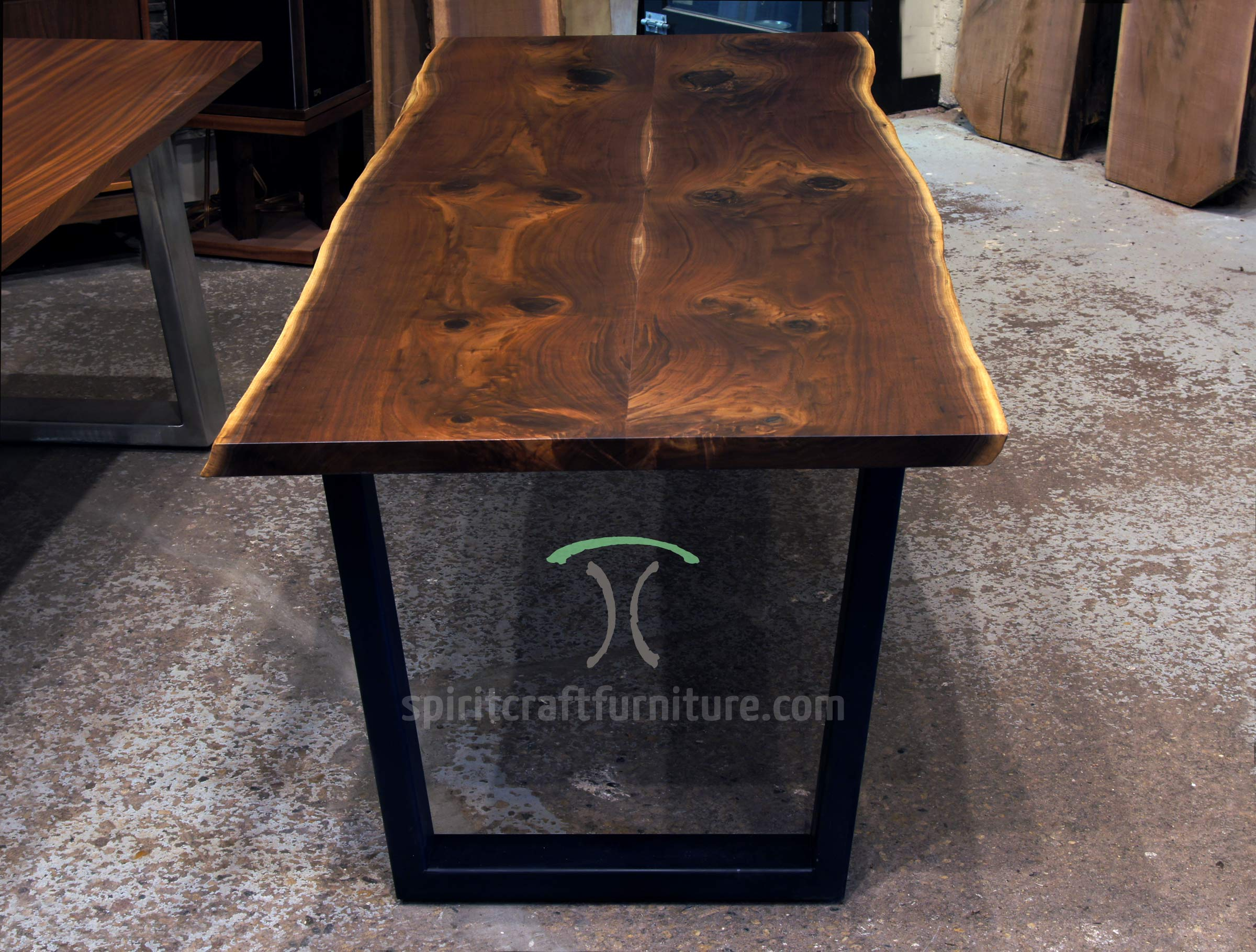 Rescued Black Walnut live edge dining table and Bench on thick steel trapezoid legs at Living Edge Furnitue Company, East Dundee, IL.