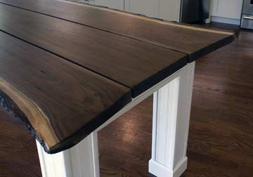 Tree shaped slab of Black Walnut with wedge to create a stunning live edge dining table of client made painted base in Fontana, WI on Lake Geneva.