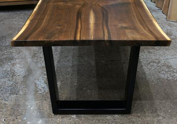 Live edge dining table in solid book-matched Black Walnut live edge slabs on massive powder coated black trapezoid legs, displayed at our retail furniture store in Chicago area, East Dundee, Illinois