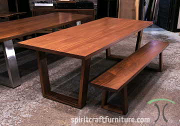 Thick slab dining or conference table in Sapele Mahogany with matching slab bench on solid hardwood trapezoid mid century modern style legs for Wisconsin client.