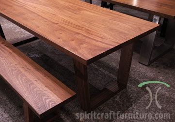 Thick slab dining or conference table in Sapele Mahogany with matching slab bench on solid hardwood trapezoid mid century modern style legs available at Spiritcraft Furniture, Dundee, IL