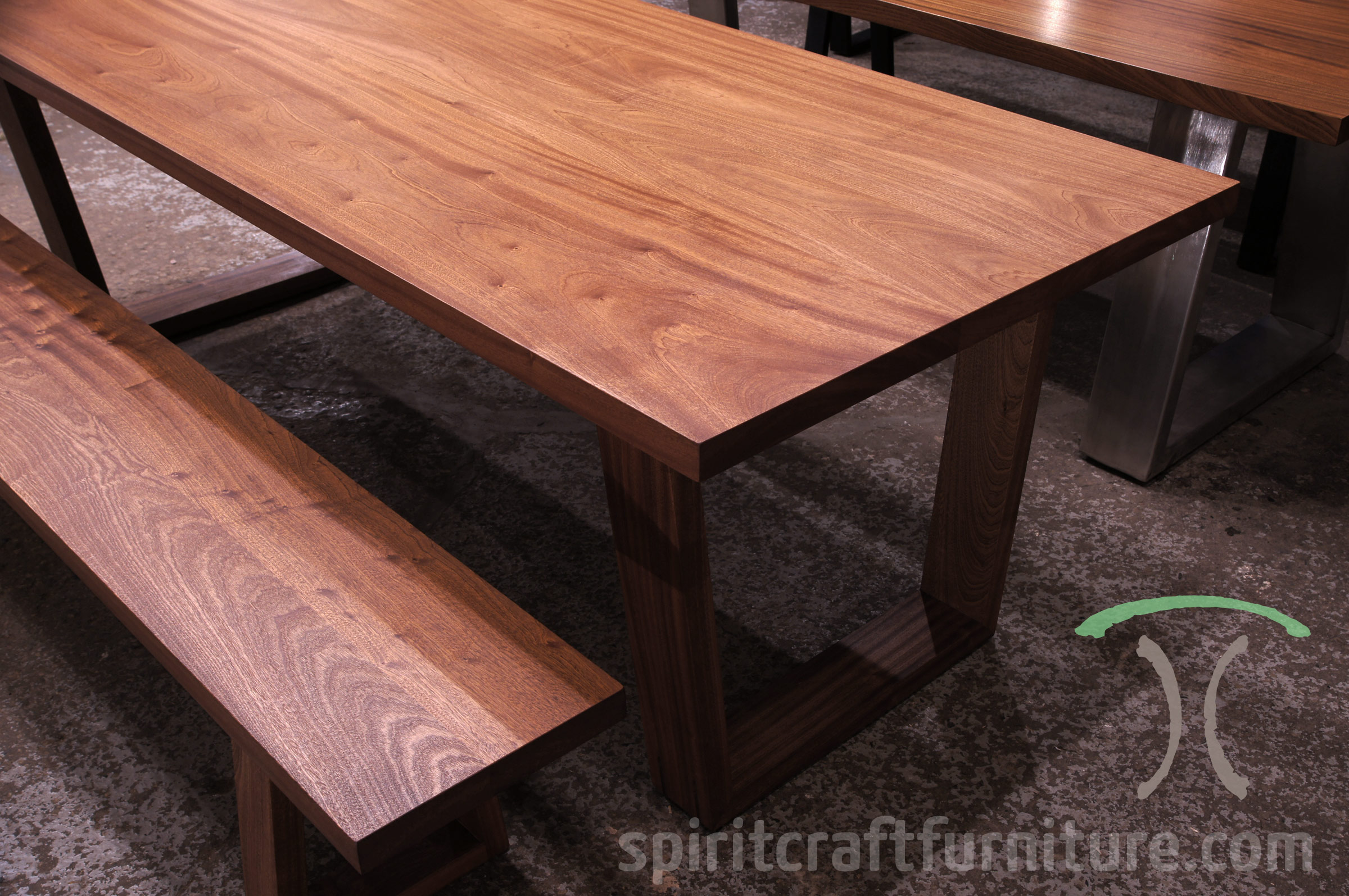 Slab dining or conference table in Sapele Mahogany with matching thick slab or plank bench on solid hardwood trapezoid mid century modern style legs available at Spiritcraft Furniture, Dundee, IL
