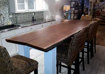 Large live edge dining table in solid Black Walnut on custom base and legs, displayed at retail furniture store in Chicago area, East Dundee, Illinois