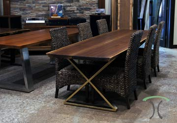 Live edge dining or conference table in solid Black Walnut on crossed gold painted steel legs, displayed at our retail slab furniture store in Chicago area, East Dundee, Illinois