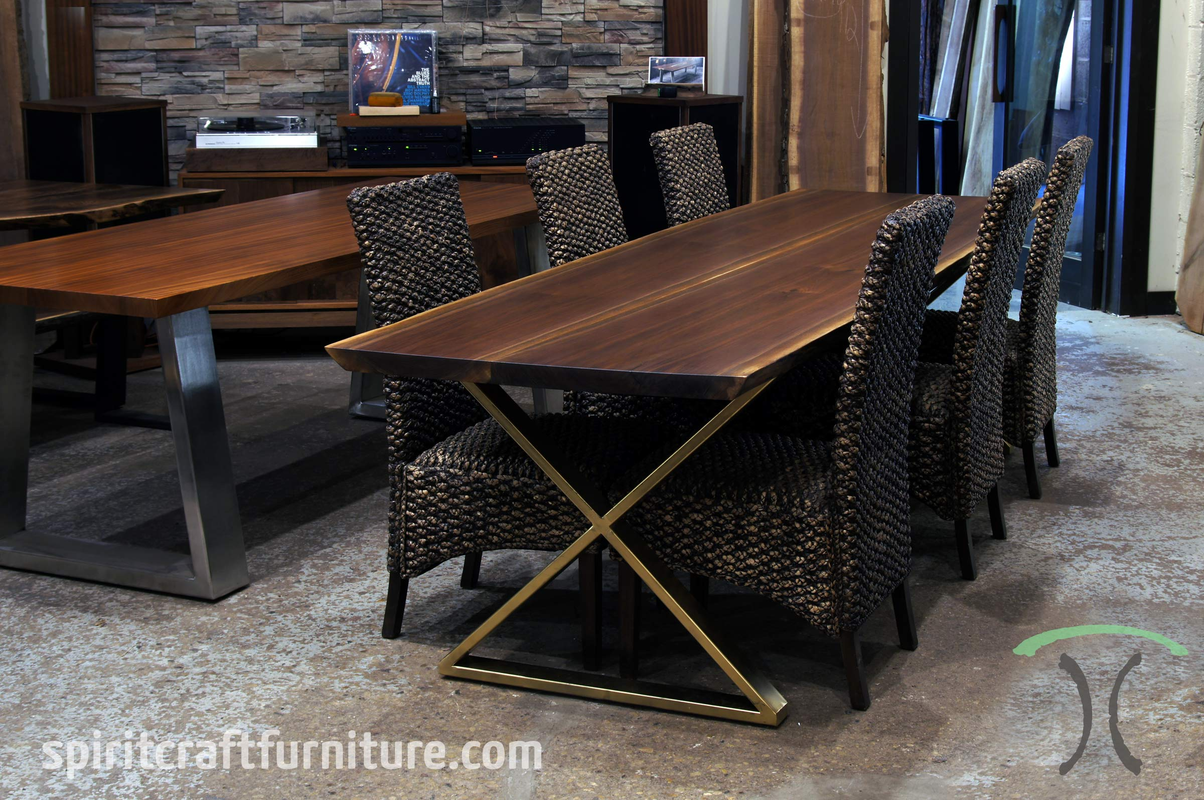 Live edge dining or conference table in solid Black Walnut on crossed gold legs, displayed at our retail slab furniture store in Chicago area, East Dundee, Illinois