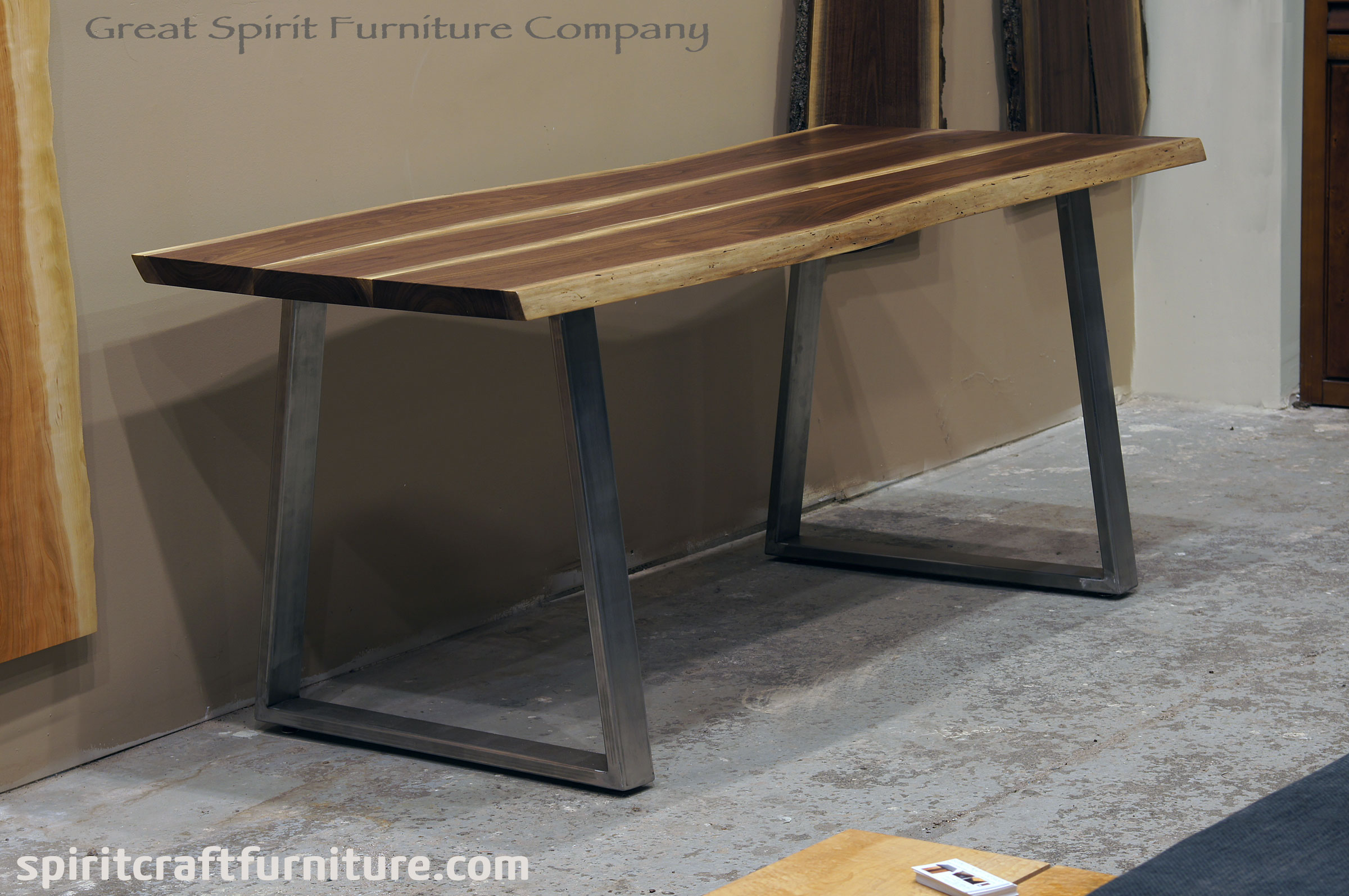 Live edge kitchen table or desk in solid Black Walnut on custom brushed stainless steel inverted trapezoid legs, displayed at our retail furniture store in Chicago area, East Dundee, Illinois