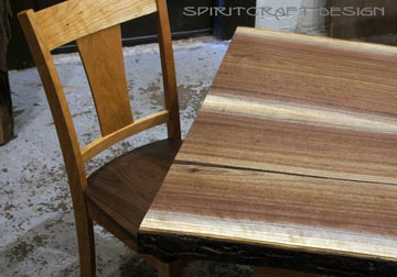 Solid hardwood dining table from slabs of kiln dried Black Walnut with mid century modern style Cherry trapezoid legs aand RH Yoder chair at Spiritcraft Design Furnitue in East Dundee, Illinois