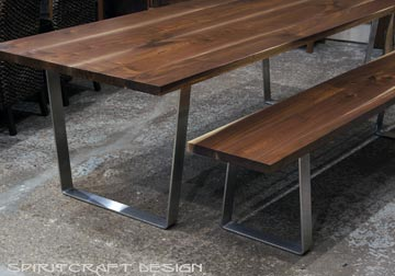 Solid hardwood dining table and bench from slabs of kiln dried Black Walnut with mid century modern style stainless steel trapezoid legs at Spiritcraft Design Furnitue in East Dundee, Illinois