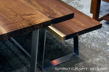 Solid hardwood dining table and bench from slabs of kiln dried Black Walnut with mid century modern style stainless steel trapezoid legs at The Great Spirit Funiture Company showroom in East Dundee, Illinois