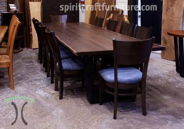 Custom made solid wood live edge slab conference or dining table in Black Walnut with steel trapezoid legs and Amish made RH Yoder Chairs by Spiritcraft Furniture, Dundee, IL.